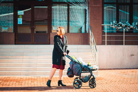 A young fashionable mother is pushing a stroller down the street. Outdoor. Side view. Walk with the baby.