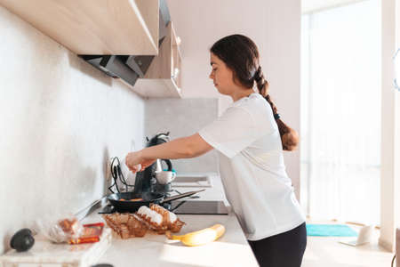 A young caucasian woman cooking breakfast in the kitchen, frying eggs. Side view. The concept of a homemade food. Stock fotó