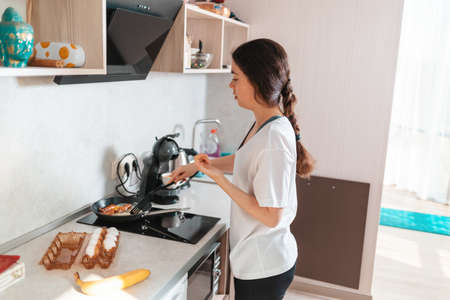 Young woman is preparing breakfast in the kitchen, frying eggs on an induction stove. Side view. The concept of a home-cooked meal.
