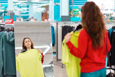 Consumerism. A young pretty woman, trying on clothes in a store, looking in the mirror. View from the shoulder. The concept of shopping during a viral pandemic.