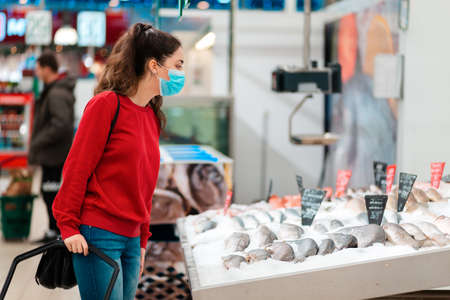 Shopping and new reality. A young woman in a medical mask on her face chooses fish in a supermarket. Side view. The concept of consumerism and grocery shopping during the coronavirus pandemic.
