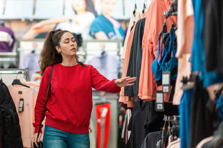 Portrait of a young beautiful woman choosing clothes in a store. Blurred traiding floor on the background. The concept of shopping and consumerism.