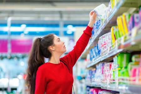 Portrait of a young pretty caucasian woman reaches to the top shelf for a pack of sanitary pads. Side view. The concept of purchasing hygiene products and cosmetics.