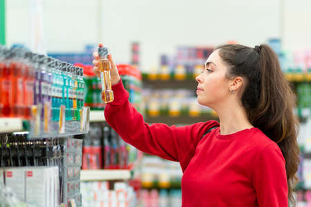 Portrait of a young woman reading information on a bottle of cosmetics. Side view. The concept of buying cosmetic products. Stock fotó