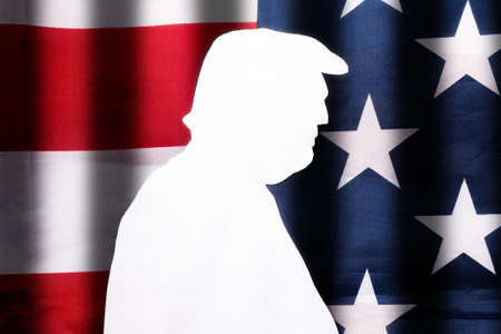 Cut out of white paper silhouette of the former President of the USA on the background of the American flag. Flat lay. The flag has dark stripes representing the grid. The concept of impeachment. Stock fotó