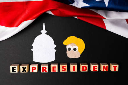 A cut out of portrait of the former president of America and the Capitol on a black background. Wooden cubes with word ex-president. Flat lay. The concept of impeachment. Stock fotó