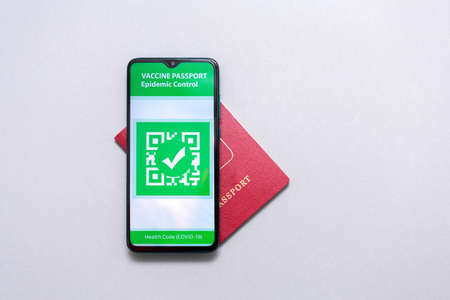 Electronic Immunity passport with a COVID-19 vaccination stamp on a smartphone screen with passport on the world map. Flat lay. Medicine and health concept. Copy space.