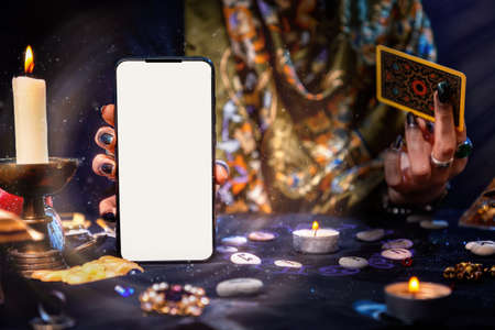 The fortune teller is holding a Tarot card and a smartphone with a white screen. Magic aura. Mock up. Close-up. The concept of divination, magic and esotericism.