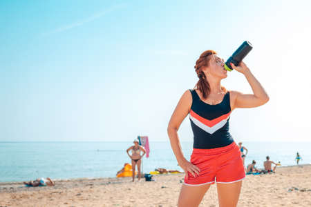 Sports and training. Cute adult woman in sportswear, posing on the beach drinking from a shaker. Copy space.
