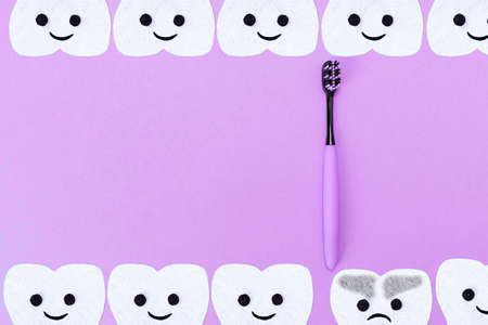 Concept of tooth care. A plastic toothbrush and cartoon teeth cut out of felt on a blue background. Flat lay. Copy space.