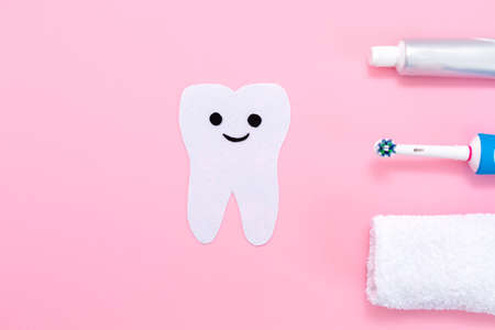 A silhouette of a tooth cut out of felt with a smiling cartoon face, next to an electric toothbrush, towel and toothpaste. Pink background. Hygiene of the oral cavity.