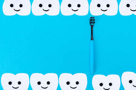 Tooth care. A plastic toothbrush and cartoon teeth cut out of felt on a blue background. Flat lay. Copy space.
