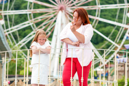Family. The mother shakes her finger at her daughter for her capricious behavior. Ferris wheel in the background. Concept of family holidays and education.
