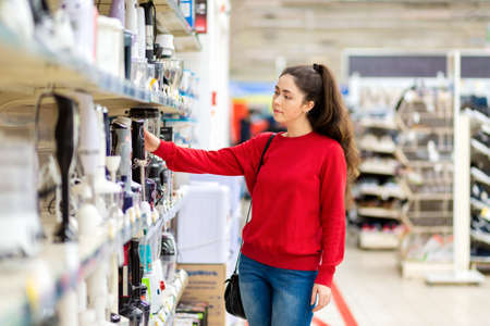 A young pretty woman chooses a blender in a home appliance store. Side view. The concept of shopping.