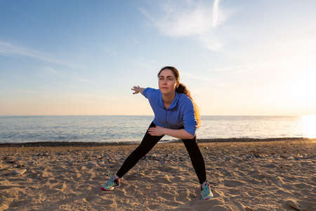 A young woman performs a warm-up on the beach. Sunset and ocean in the background. Wellness and sports lifestyle.