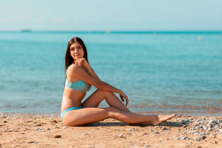 A beautiful young woman in swimsuit sitting on the ocean beach and posing. The concept of summer vacation.