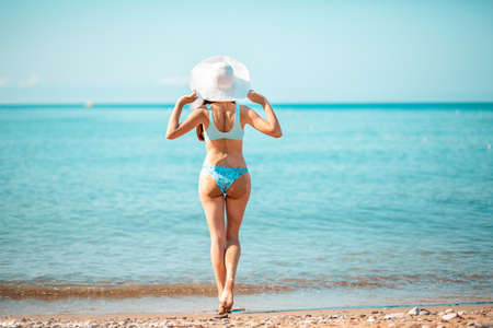 A young beautiful woman in a straw hat poses on the ocean. The view from the back. The concept of a holiday at a seaside resort.