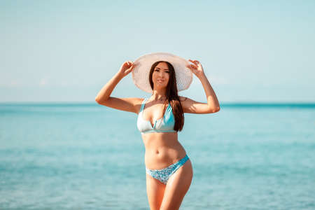 A young beautiful woman in a straw hat poses standing on the ocean. Concept of a holiday at a seaside resort.