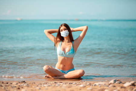 Summer. A young caucasian woman in a protective mask, sitting crossed legs on the oceans beach. The concept of vacation during the coronavirus pandemic.