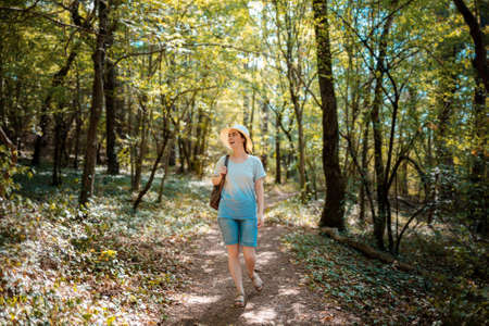 A young happy woman walks through the forest. Summer outdoor activities. Stock Photo