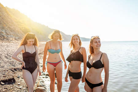 A group of young women with a diverse body shape pose in swimsuits. Sunlight. In the background-the sea and sky.Copy space. Concept of vacation, holiday at the sea and bodypositive.