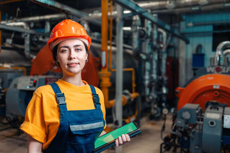 Industrial production concept. Portrait of a female engineer in uniform and helmet with a tablet in her hand. In the background-boiler equipment.