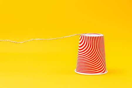 Close up of paper cup connected by a string. Children's homemade toy-walkie-talkie. Yellow background. Copy space. The concept of communication.