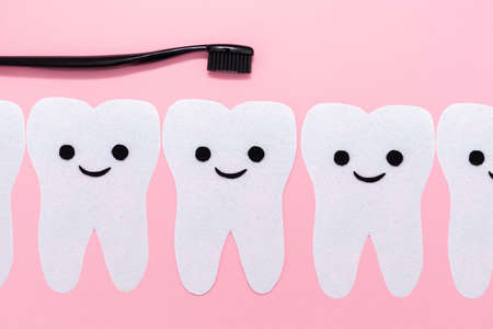 Concept of oral hygiene. The teeth cut out of felt with a smiling cartoon face. Black plastic brush. Pink background. Flat lay. Copy space.