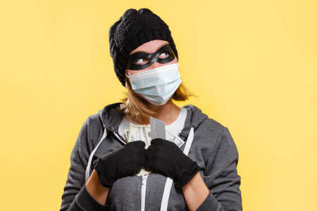 The new normal. A female hacker wearing a black hat, gloves, and protective mask holds a wad of dollars. Yellow background. The concept of crime.