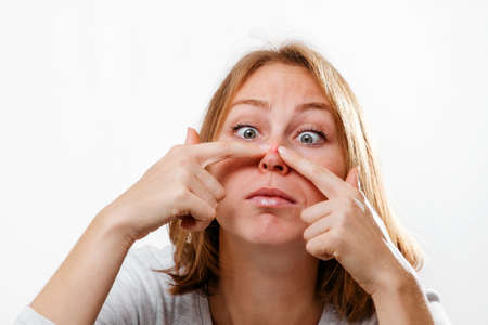 Portrait of a young woman squeezing out a pimple on her nose. White background. The concept of acne and skin problems. Stockfoto