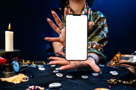 Astrology. Witch's hands hold a cellphone with a white screen. Mock up. The concept of divination and predictions with the help of modern technologies.