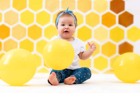 A happy toddler girl is sitting on a white floor with yellow balloons. In the background is yellow honeycombs. The concept of the World Children's Day.