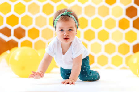 Celebrating. A toddler girl crawling on a white floor with yellow balloons. In the background is yellow honeycombs. World Children's Day. 版權商用圖片