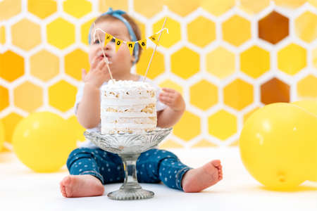 First birthday. A blurred toddler sits next to a cake and eats a piece with her hands. In the background, a design of yellow honeycombs and balloons.