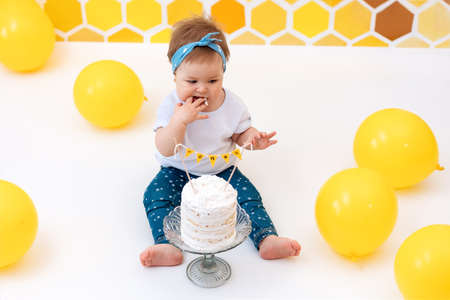 A toddler sits next to a cake and eats a piece with her hands. In the background, a design of yellow honeycombs and balloons. Top view. First birthday concept. 版權商用圖片 - 167045145