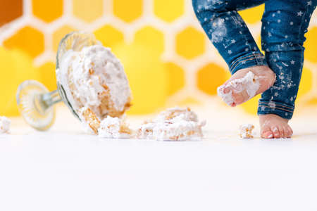 A small child's feet smeared in cream, and a cake lying on the floor in close-up. In the background is a pattern of yellow honeycombs and balloons. Copy space. Smash cake concept. 版權商用圖片