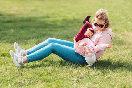 A young mother is sitting on the grass, playing with her baby. Recreation in the park with a child. Top view. Children's day.