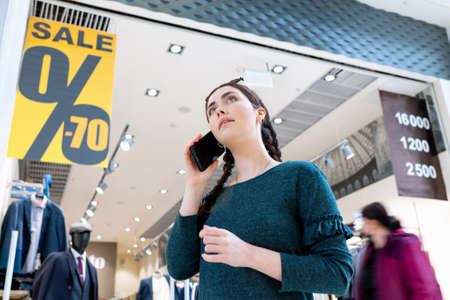 A young woman communicates on the phone. In the background, there is a store and posters with a sale. The concept of communication and consumerism. 版權商用圖片 - 167018694
