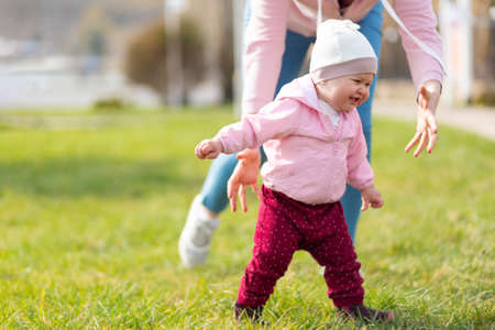 A happy baby girl runs away from her mother. Family games in the park. Children's day concept. 版權商用圖片