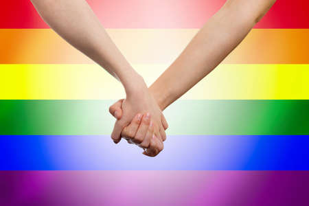 Female's hands hold each other against the background of a rainbow LGBT flag. Close-up. The concept of LGBT equality.