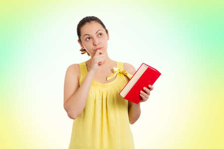 A young pensive woman in a yellow dress holds a book in her hands. Copy space. World Book Day concept. 版權商用圖片