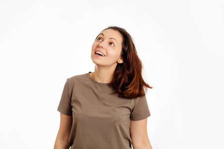 A young woman smiles and looks up. White background. Copy space. The concept of positive human emotions. 版權商用圖片 - 167196264