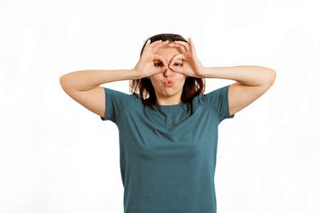 A young Caucasian woman makes a face. White background. The concept of April Fools' Day.