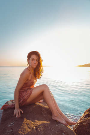 Beautiful woman in lingerie posing on a coastal cliff. Sea and sunset in the background. Vertical orientation. Wild look.