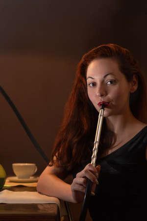 Young beautiful woman in black dress smokes a hookah or shisha in the night club or bar smoke.