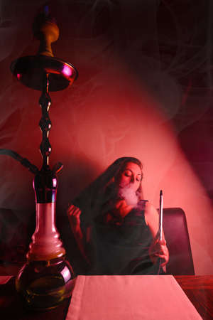 Woman Smoking hookah and posing for the camera. Around circles of steam and smoke. Red tint. 版權商用圖片 - 167196332