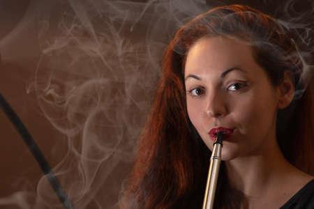 Young beautiful woman in black dress smokes a hookah or shisha in the night club or bar smoke. Smoke and steam in the air. Close up. 版權商用圖片
