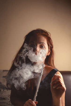 A sexy young woman smokes a hookah and releases a cloud of steam through her nostrils. Dangers of smoking concept. 版權商用圖片