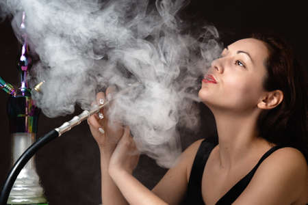 A beautiful young woman in a black dress smokes a hookah and lets out a cloud of steam. The atmosphere of relaxation and pleasure. Close up.
