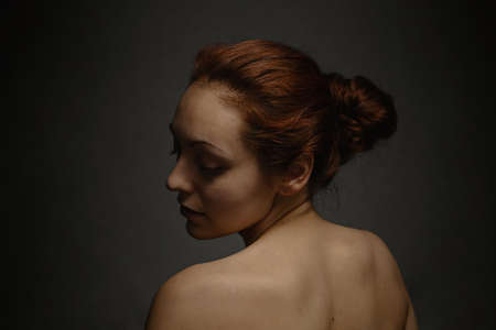 Tan woman with ginger hair close her eyes and posing on a camera. The view from the back. Dark background.